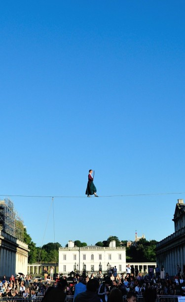 Photograph of a funambulist walking the tightrope suspended between the twin domes of the Old Royal Naval College during Greenwich+Docklands International Festival 2018